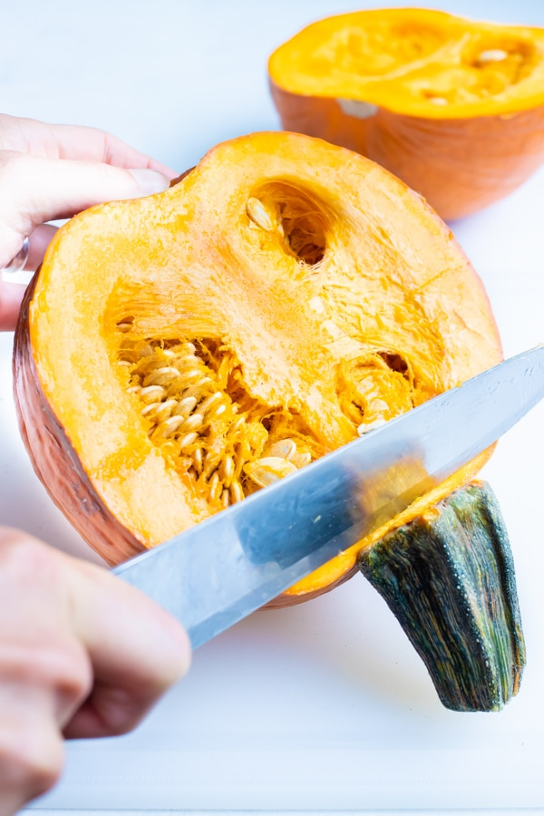 A knife is used to make an incision at the pumpkin stem.