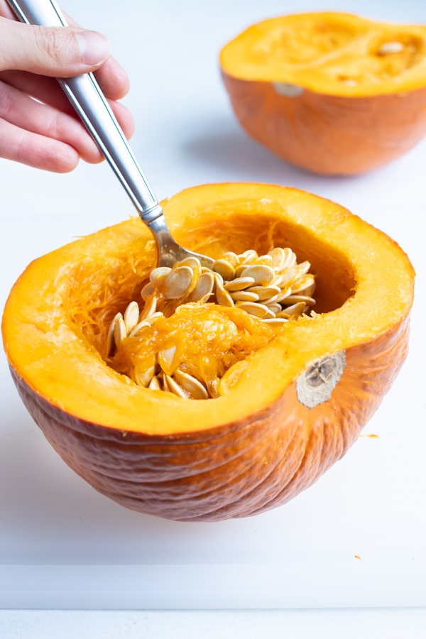 Insides are removed from the pumpkin halves with a spoon.