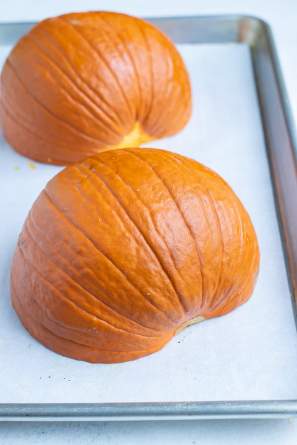 Pumpkin halves are laid hollow-side down on the baking sheet.