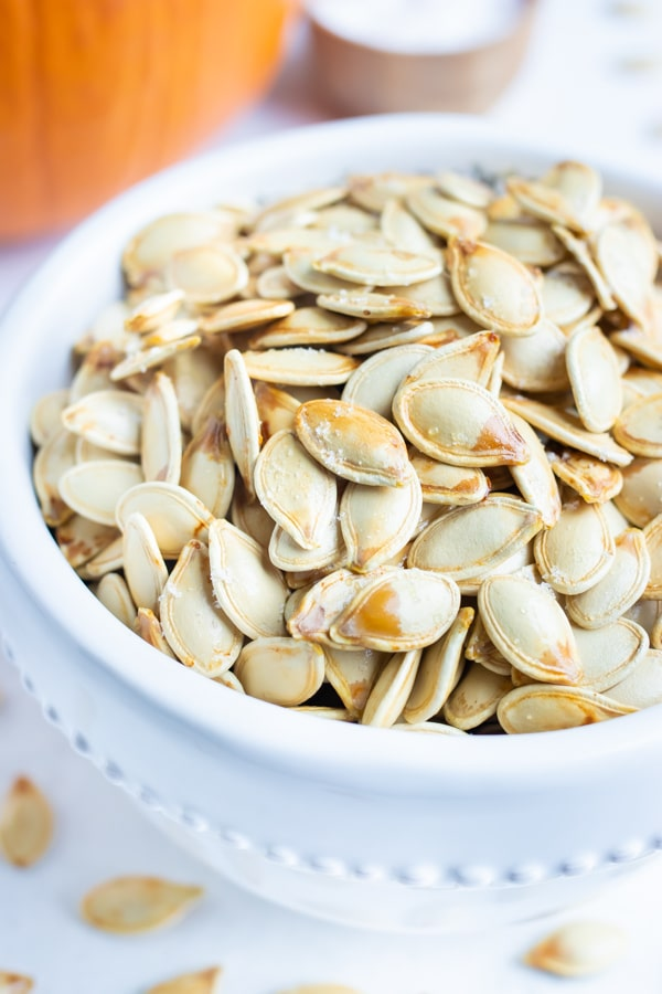 Baked pumpkin seeds are in a white bowl for a healthy snack.