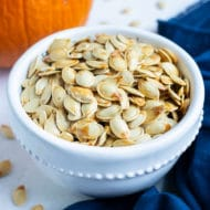 Pumpkin seeds are placed in a white bowl on the counter in this fall recipe.