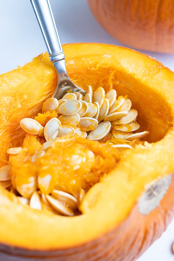 A fresh pumpkin is cleaned out before seeds are roasted.
