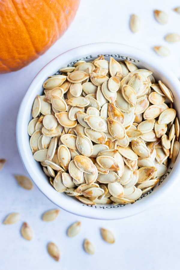 Roasted pumpkin seeds are placed in a bowl before being used in soups and salads.