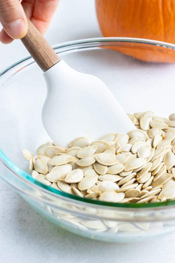 Oil or butter, pumpkin seeds, and seasonings are combined in a bowl and mixed.