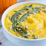Pumpkin soup is topped with sage leaves and pumpkin seeds for an easy and stunning appetizer.