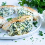 Low carb stuffed chicken dish is filled with a homemade spinach artichoke dip and cooked on the stove.