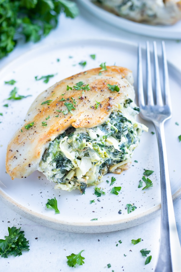Stuffed chicken breast is plated for an easy, low-carb dinner.