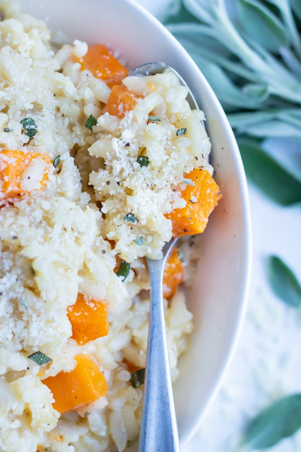 A spoon is used to enjoy homemade butternut squash risotto with sage.