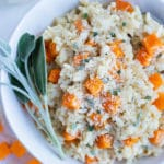 Roasted butternut squash risotto with sage is served in a white bowl on the counter.