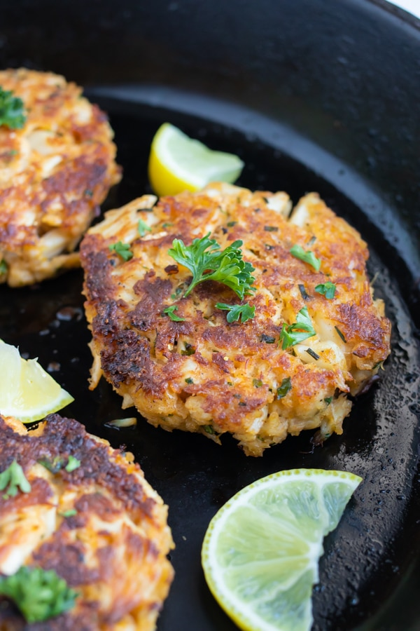 Gluten-free crab cakes are seared in a skillet.
