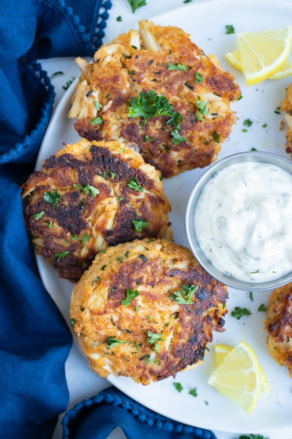 Easy gluten-free crab cakes are served with a tartar sauce.
