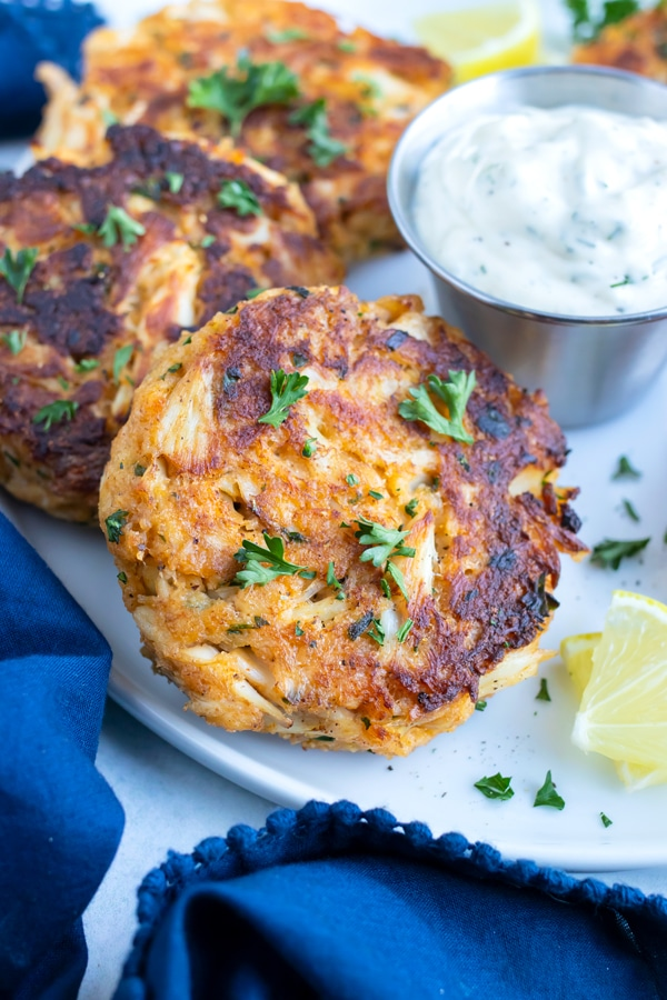 Crab cakes that were baked in the oven are served on a plate.