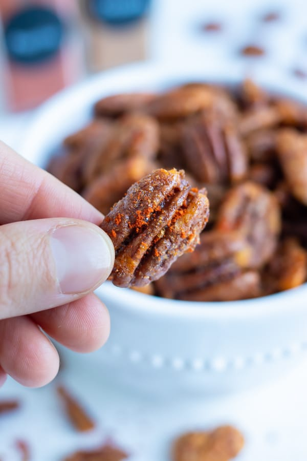 A spiced pecan is held up by a hand for a low-carb snack.