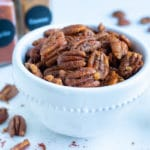 Spiced pecans are kept in a white bowl for snacking.