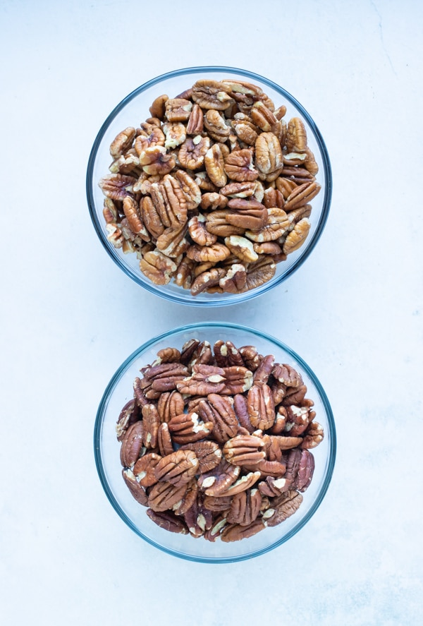 Raw pecans are placed in a bowl before being roasted.