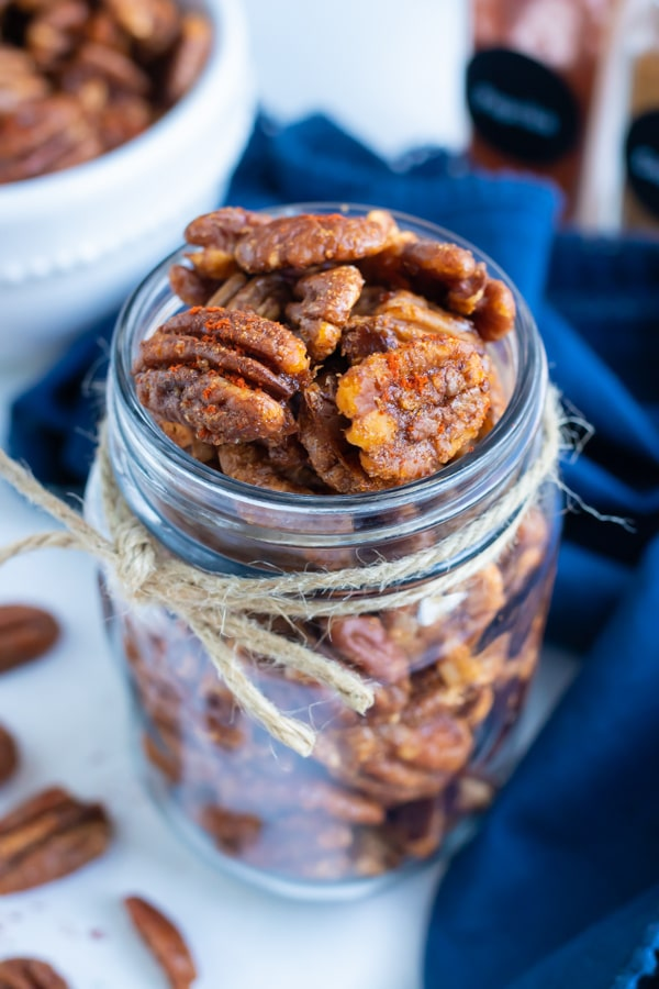 Roasted spiced pecans are kept in a mason jar for a savory food gift.