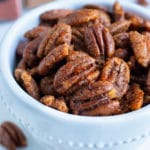 Oven toasted pecans are put in a bowl on the counter for a keto snack.