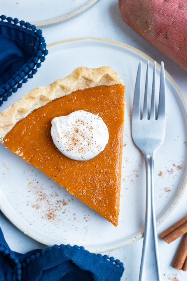A fork lays beside a slice of sweet potato pie.