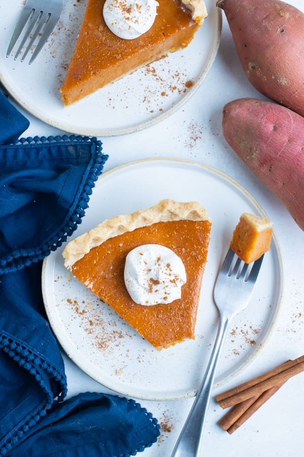 Sweet potato pie is cut into slices and served on white plates for Thanksgiving.