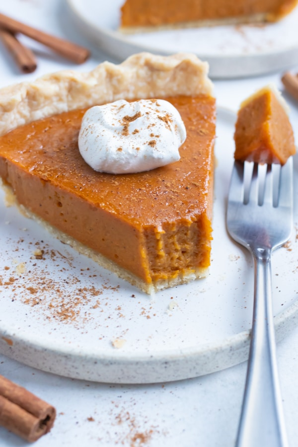 Creamy sweet potato pie is topped with whipped cream and a sprinkle of cinnamon for a vegetarian dessert.