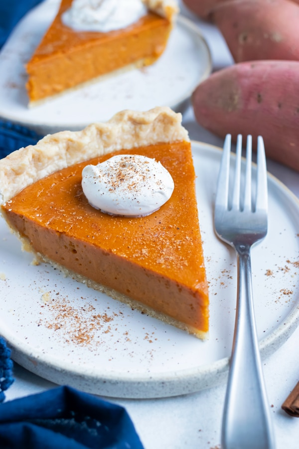 Gluten-free sweet potato pie is served with a fork and topped with whipped cream.