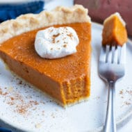 Sweet potato pie served on a plate with a dollop of whipped cream on top.