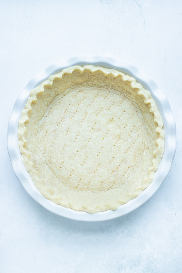 Homemade gluten-free pie crust is parbaked in the oven.