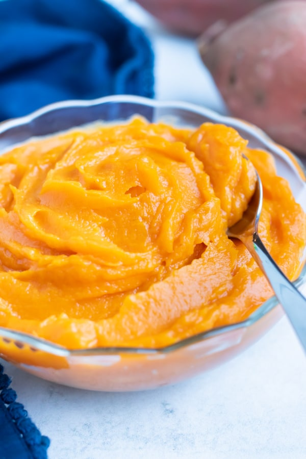 Homemade sweet potato puree in a glass bowl has a smooth and creamy texture.