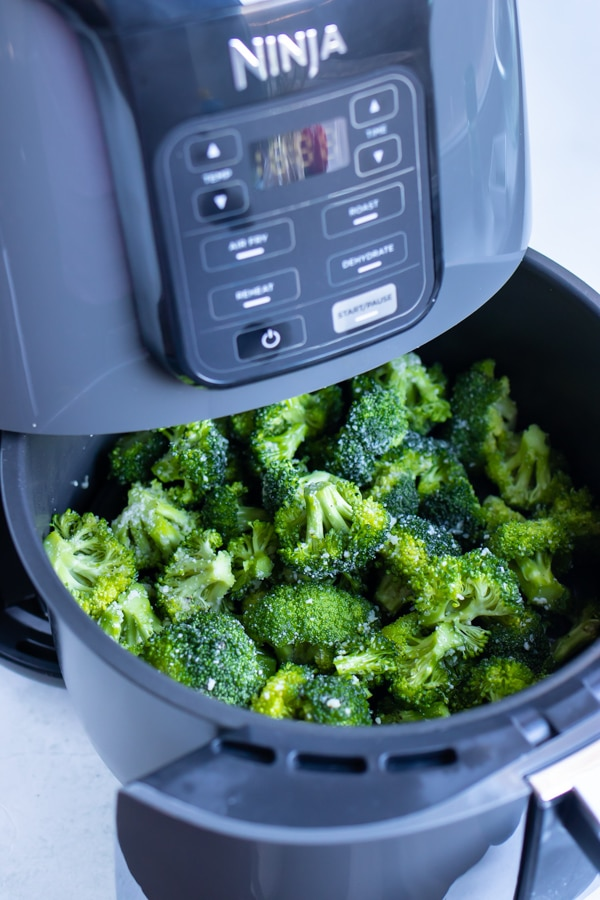 Broccoli is put inside the Ninja air fryer to be roasted.