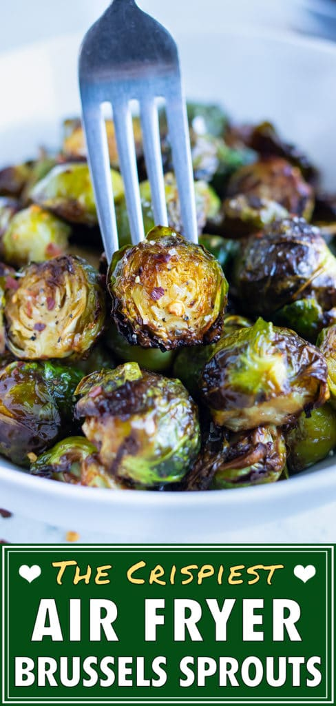 A crispy brussels sprout is lifted up by a fork out of a bowl.