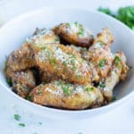 Crispy air fryer chicken wings are served in a white bowl on the counter.