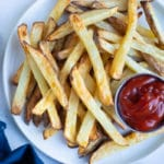 Homemade french fries are served on a plate for a side.