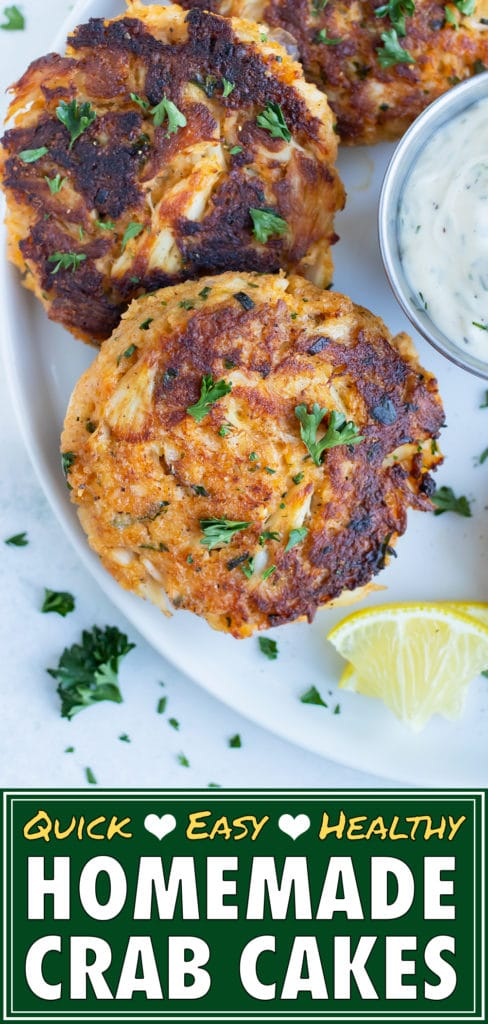 Homemade crab cakes are served on a white plate with fresh lemon and tartar sauce.