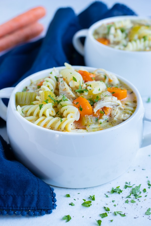 Two bowls of dairy-free, gluten-free chicken noodle soup are served on the counter.