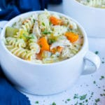 A white bowl is filled with chicken noodle soup that is made with gluten-free noodles.