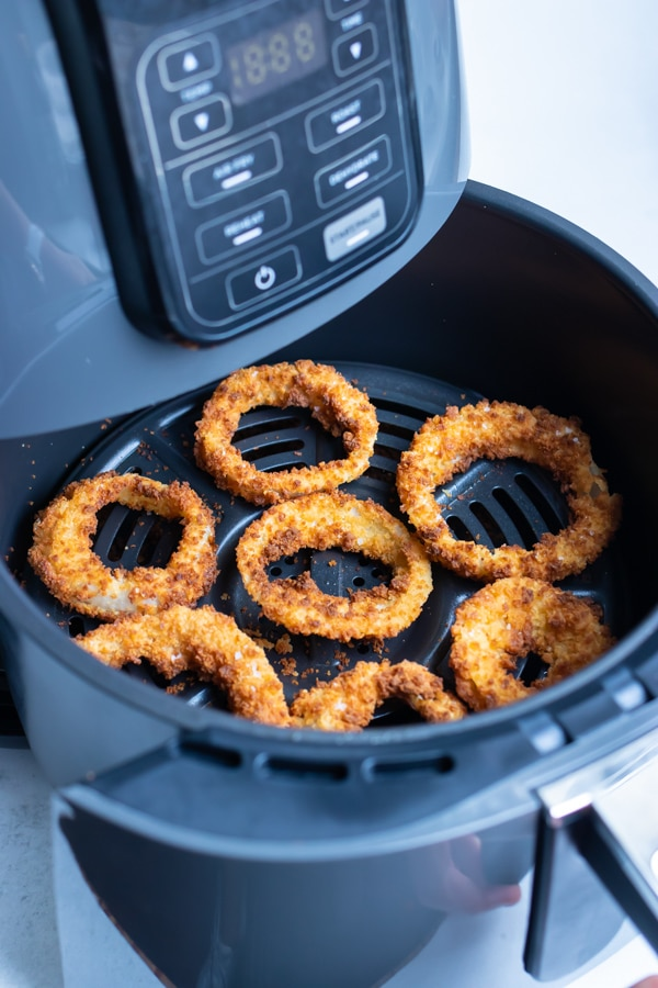 A layer of golden, crispy onion rings are shown in the air fryer.