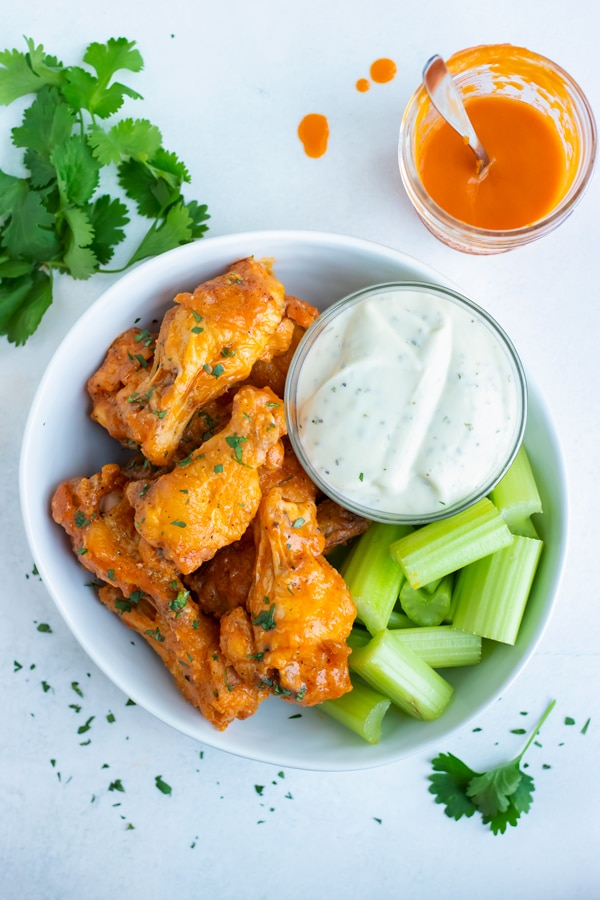 Baked buffalo chicken wings are served with blue cheese dressing and celery.