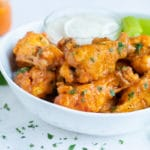 Baked buffalo chicken wings are served with ranch dressing and celery for an appetizer.