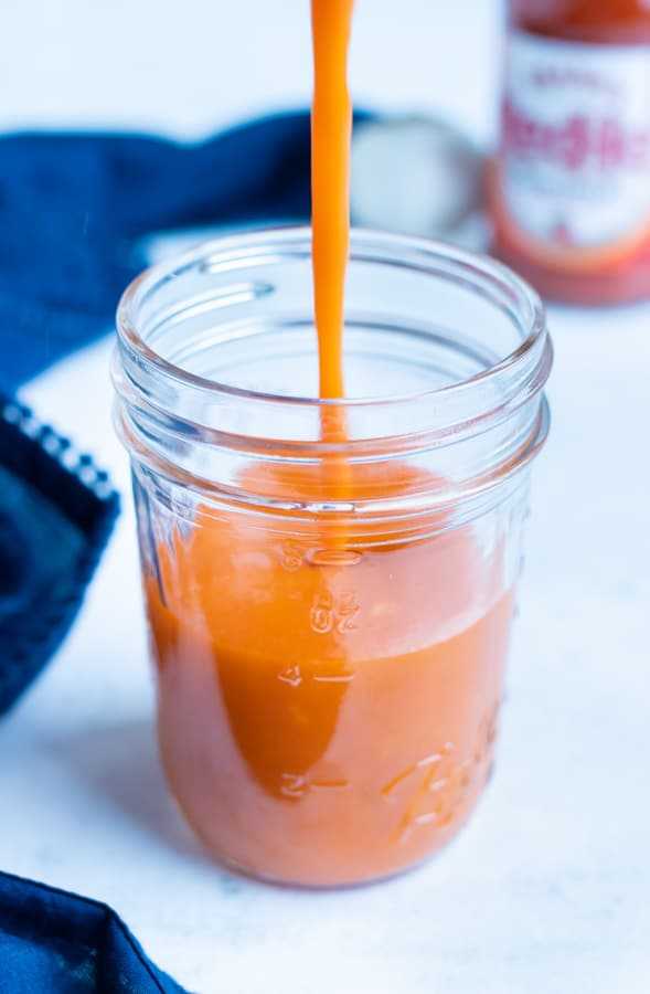 Buffalo wing sauce is poured into a mason jar.