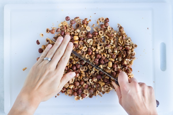 The roasted hazelnuts are chopped finely before blending.
