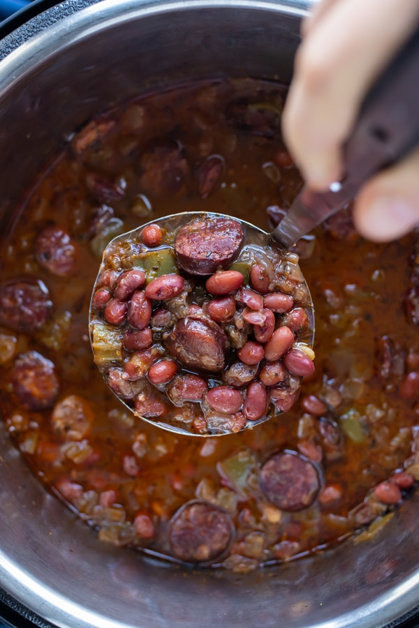 A ladle lifts up a serving of red beans and rice.