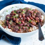 Instant pot red beans and rice are served for dinner in a white bowl.