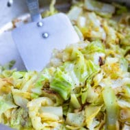 The caramelized, sautéed cabbage is stirred with a spatula.