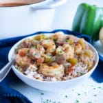 Sausage and shrimp gumbo is served with rice in a white bowl for dinner.