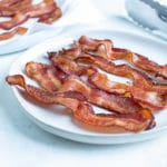 Bacon is placed on a white plate on the counter.