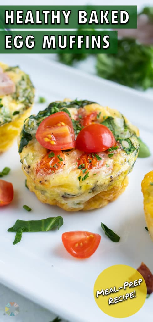 Three breakfast egg muffins are served one a plate with fresh tomatoes and herbs.