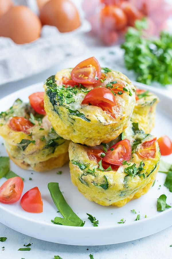 A pile of four spinach egg muffins are served on a white plate.