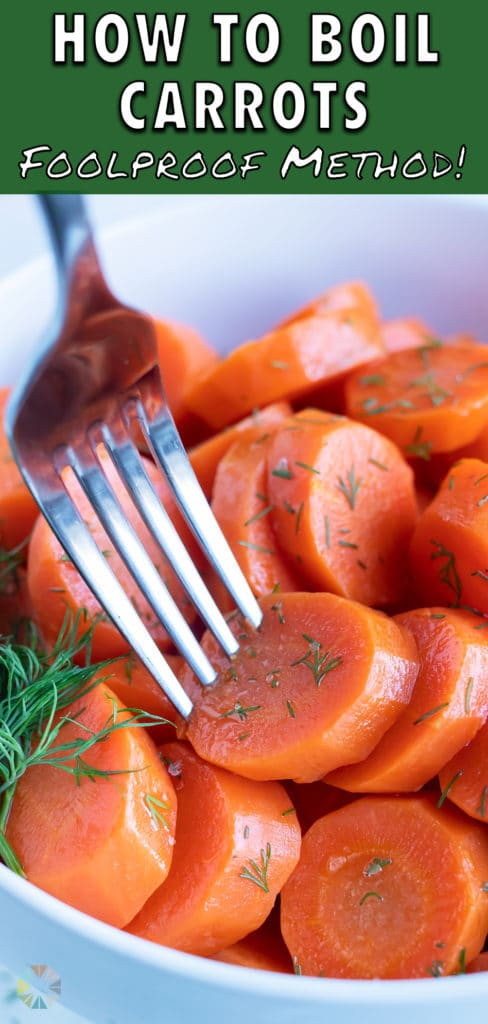 A sliced boil carrot is served with a fork.