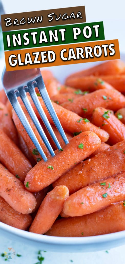 A glazed carrot is lifted up by a metal fork from a bowl.
