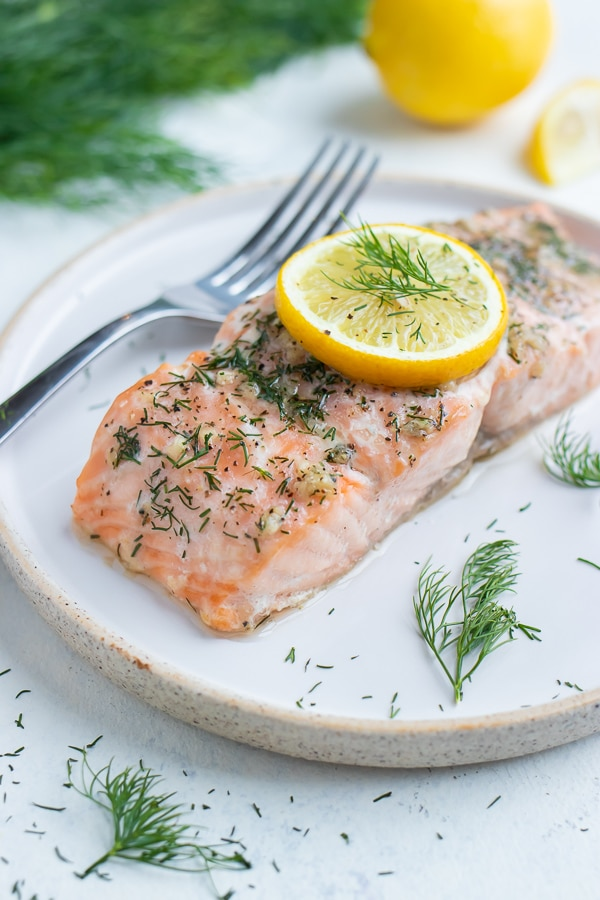 Lemon and dill salmon is served on a white plate with a fork.